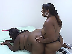 BBW lesbos use a strap-on dildo to fuck